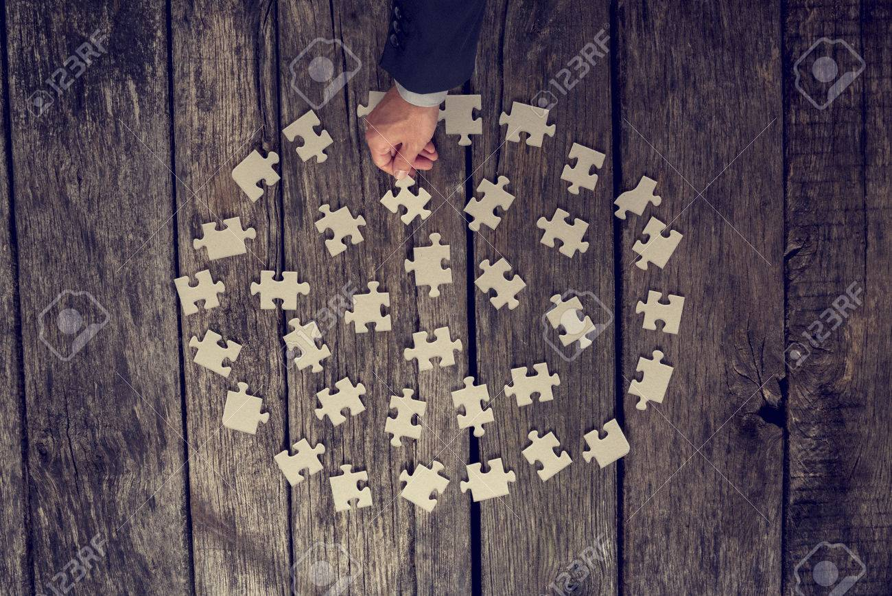 Man Choosing A Puzzle Piece From A Neatly Arranged Circle Of Stock