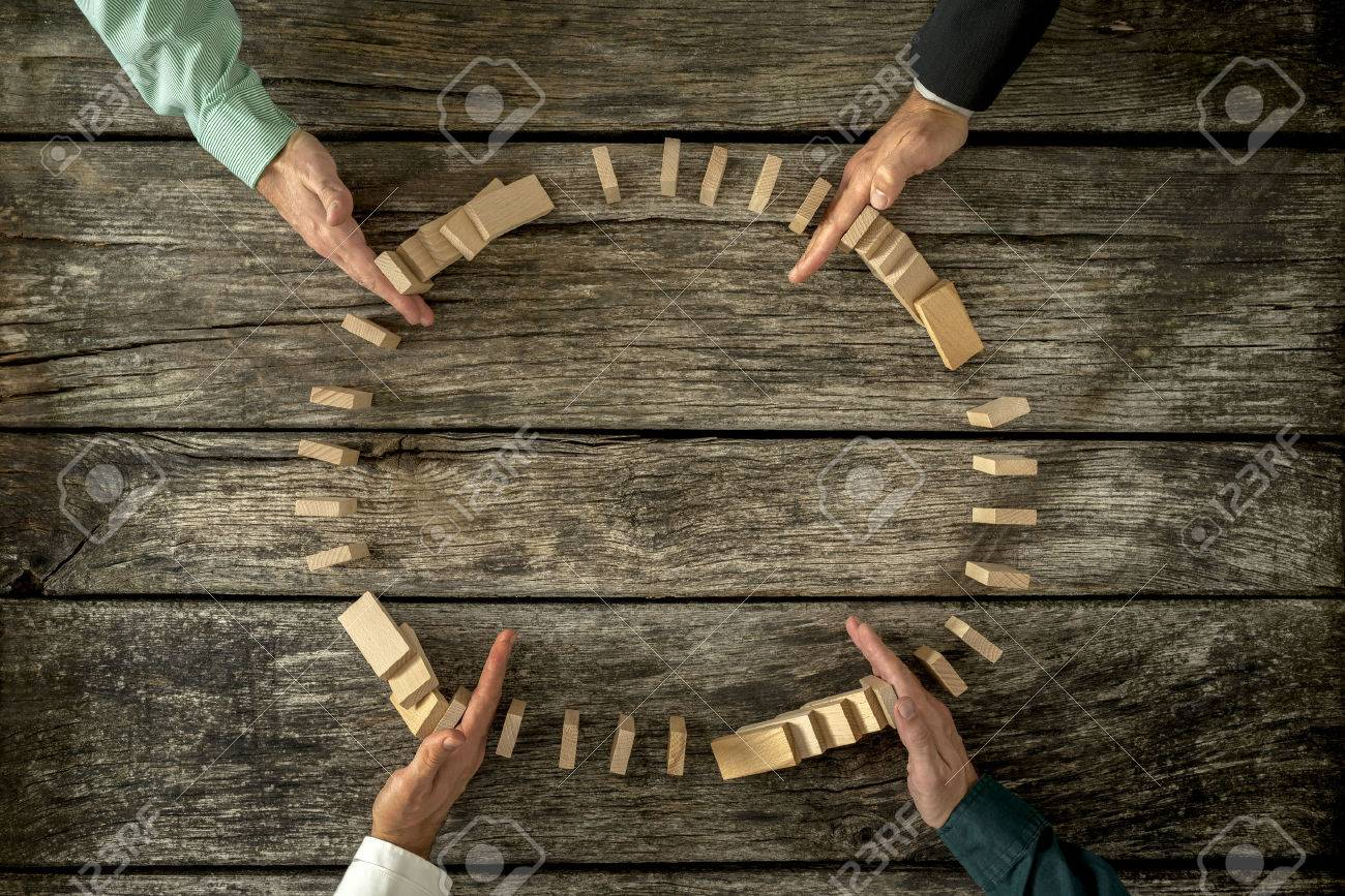 Hands of four businessmen joining forces as a team to stop wooden pegs from falling. Business concept of teamwork, crisis solution and problem management. - 48052286