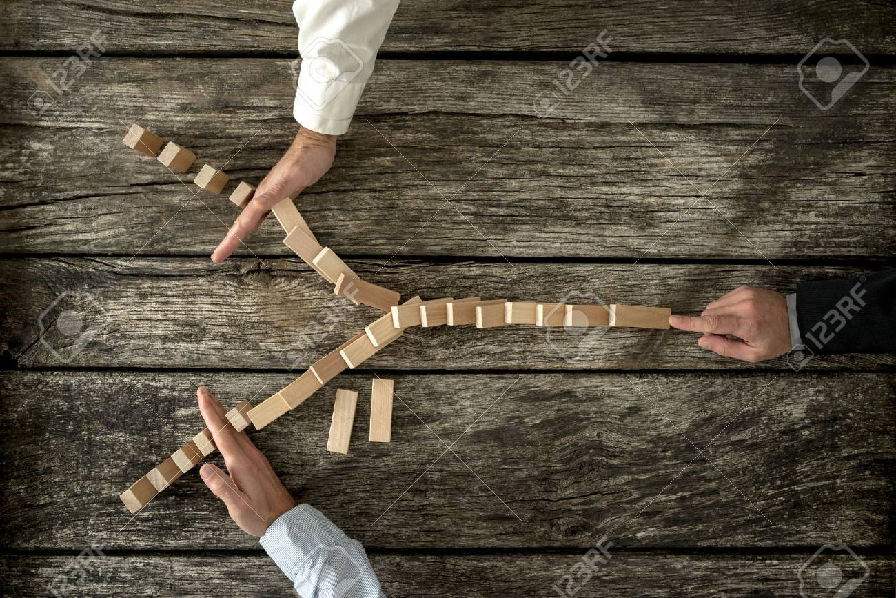 Top view of male hand pushing dominos placed in Y shape knocking them down and two other hands stopping them each on one side. Conceptual of crisis management in business. - 48351369
