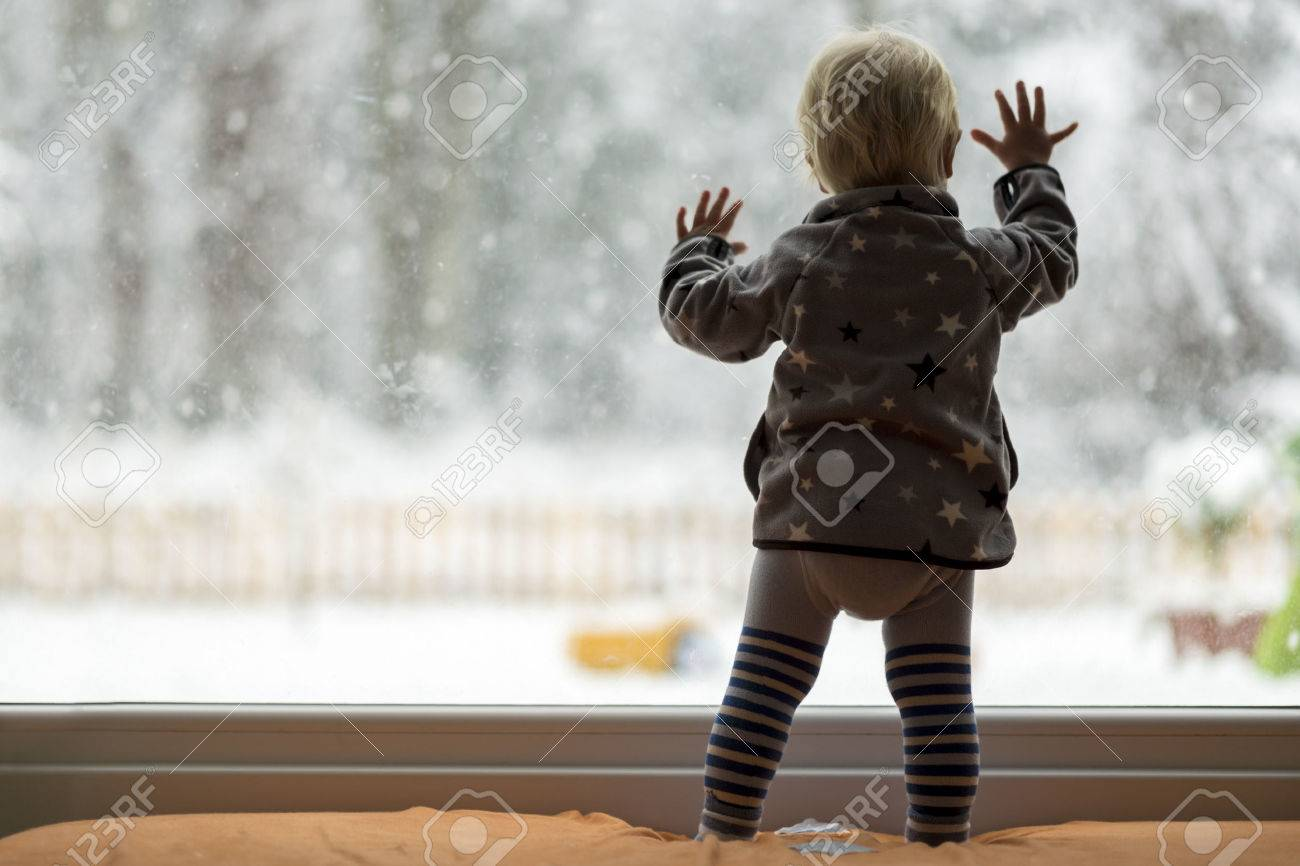 View form behind of toddler child standing in front of a big window leaning against it looking outside at a snowy nature. - 50415994