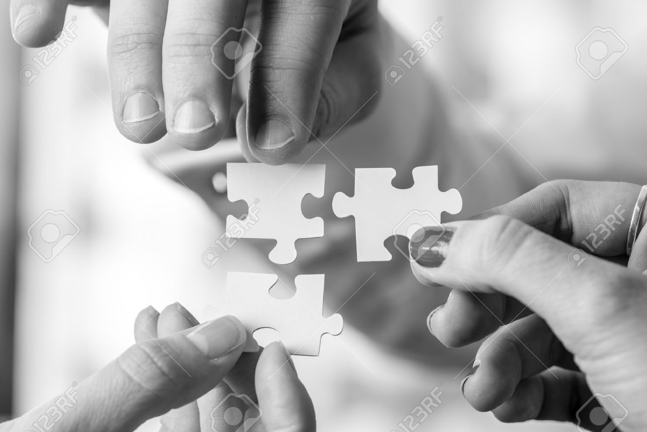 Black and white image of three people, male and female, holding puzzle pieces to match them. Conceptual of teamwork, cooperation and problem solving. - 51268023