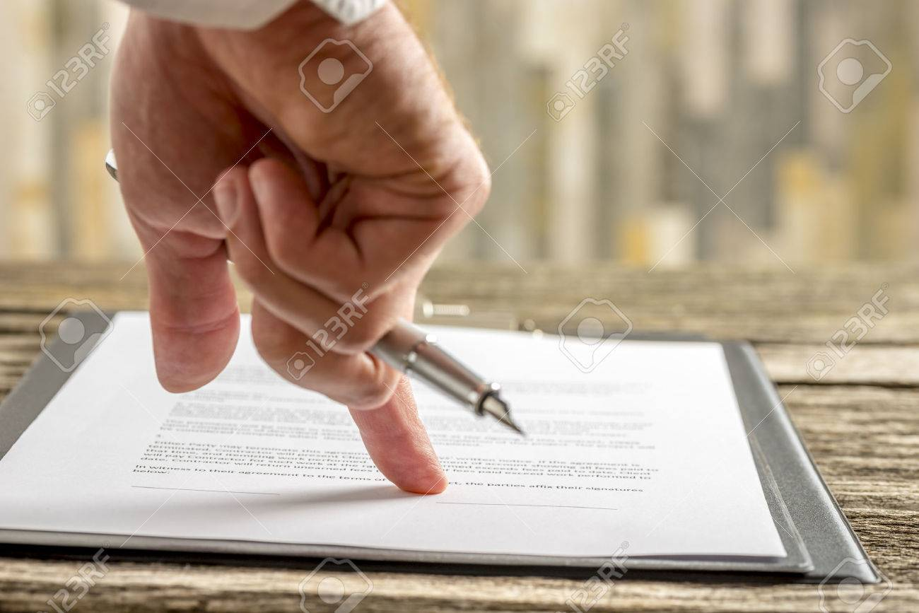 Closeup of male hand holding a pen pointing to a line at the end of a contract, document or application form ready for signature. - 51268026