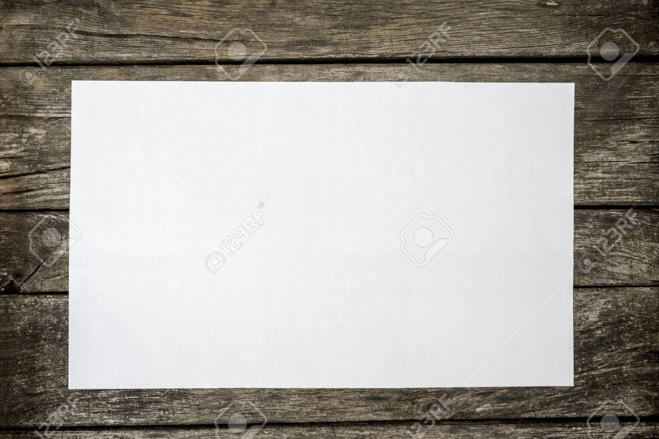 Top view of blank white piece of paper on a textured rustic wooden desk. - 54674763