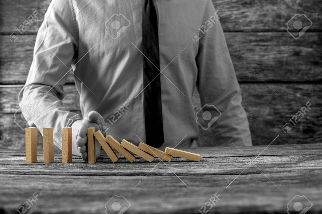 Greyscale image of businessman stopping falling dominos with his hand with selective colour of the dominos. - 56777799