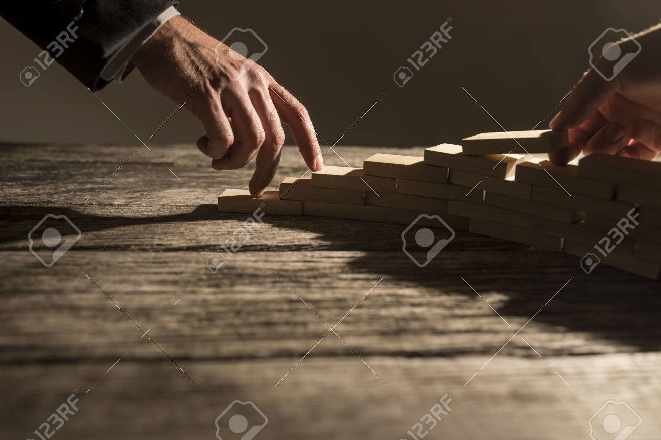 Closeup view of businessman arranging wooden pegs in to a staircase like structure for his colleague to walk his fingers up the steps. Conceptual of business cooperation, vision and success. - 56777819