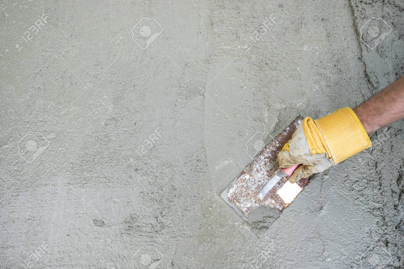 Workman or builder doing plastering of a concrete surface, top view of his hand and tool in a DIY, renovation and construction concept, with copy space. - 113556420