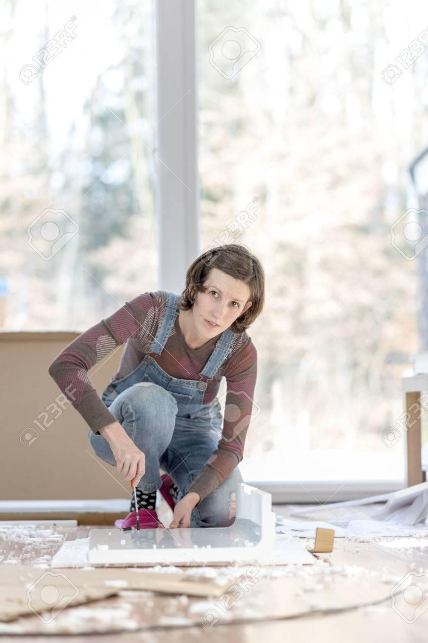 foto de archivo mujer adulta joven sola en un mono de trabajo en el piso con muebles viejos o proyectos en el hogar with con muebles viejos