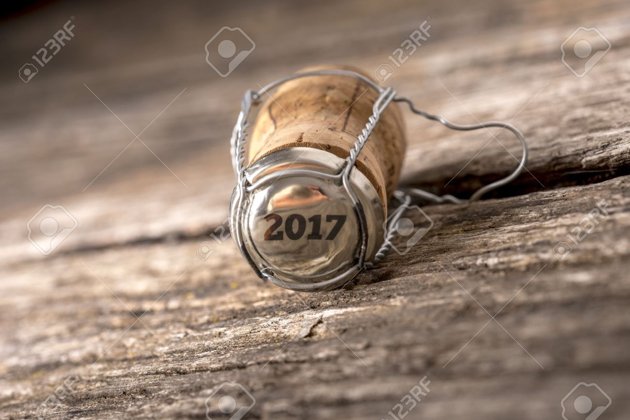 The year 2017 stamped as number on wine bottle cork over weathered old wooden table. - 62118064