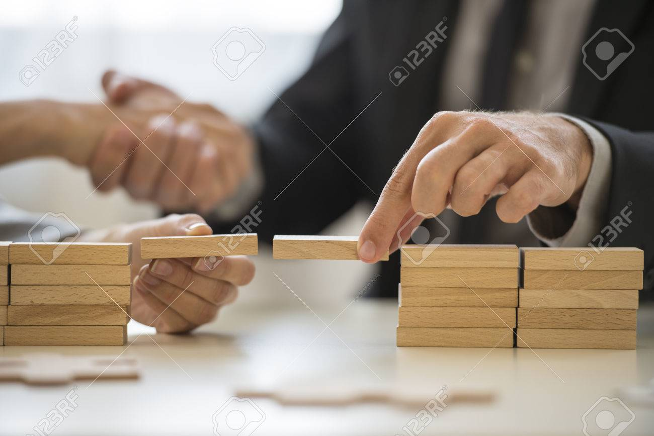 Teamwork or building bridges concept with a businessman and woman holding wooden building blocks to form a bridge over a gap while clasping hands in the background. - 65015027
