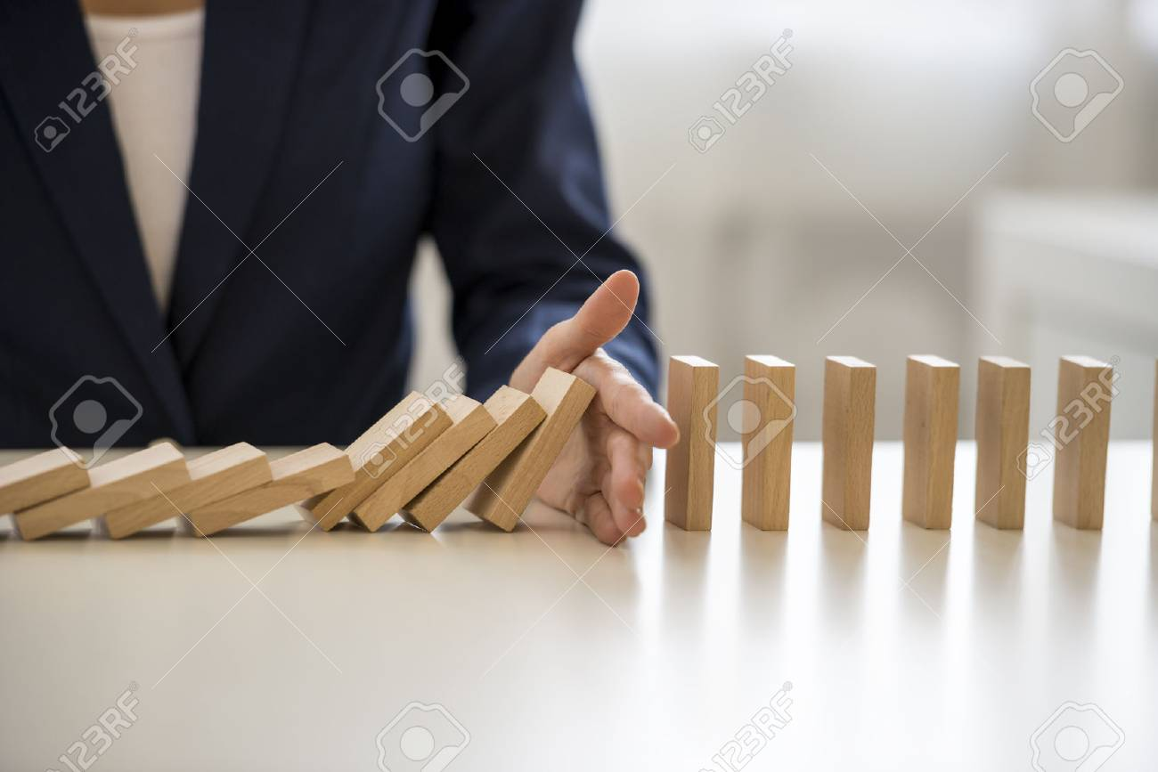 Close up view on hand of business woman stopping falling blocks on table for concept about taking responsibility. - 65855074
