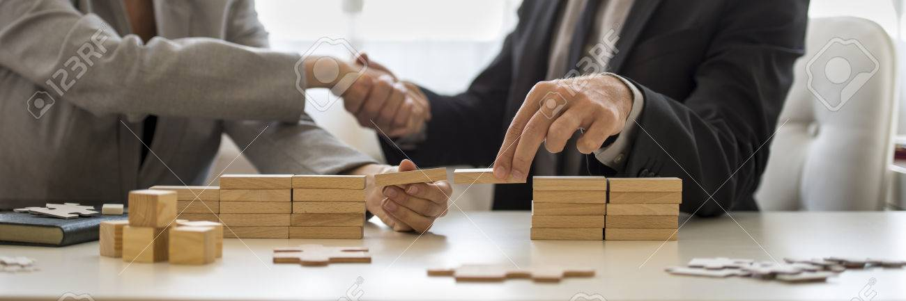 Businessman and businesswoman holding wooden building blocks to form a bridge over a gap while shaking hands. - 68139743