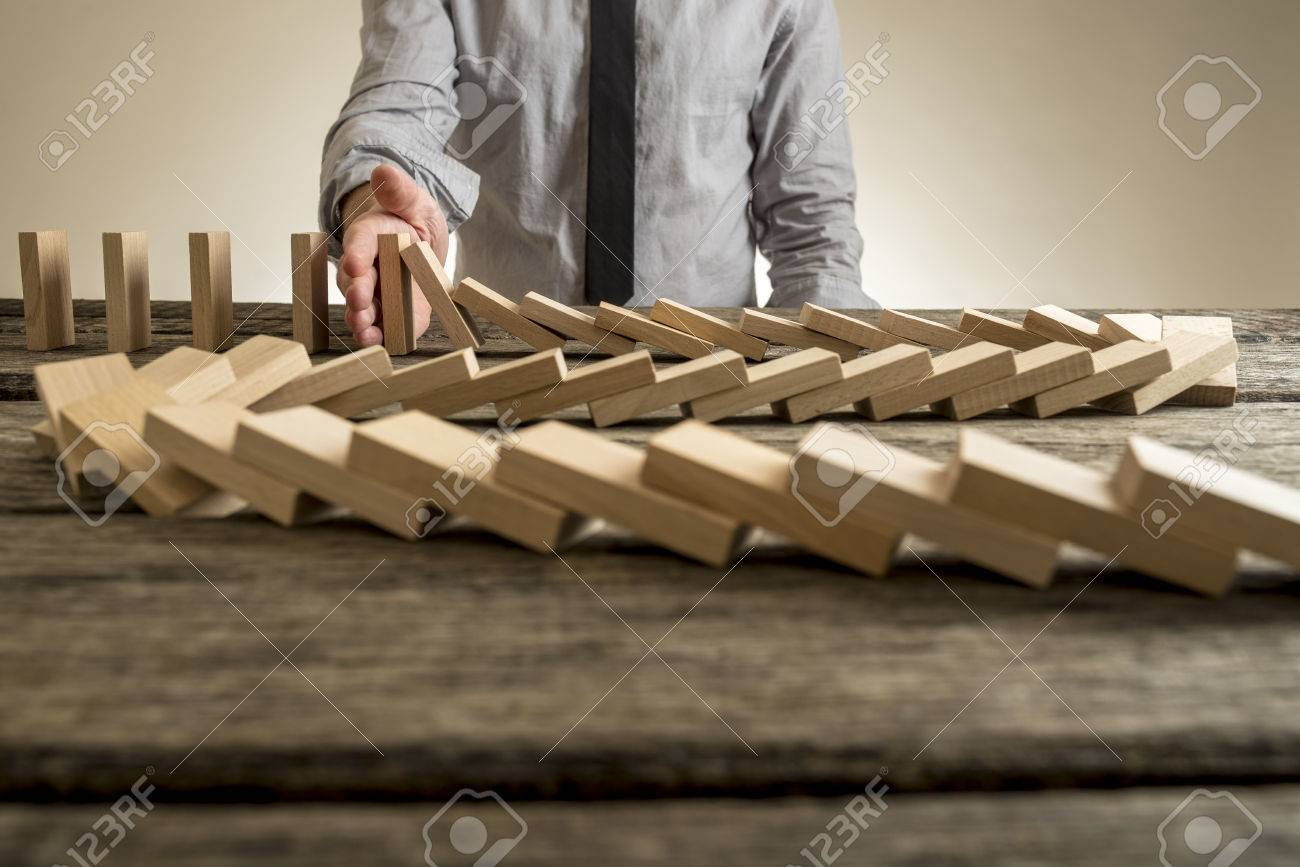 Hand stopping domino effect of wooden blocks for concept about business and accountability. - 70847764