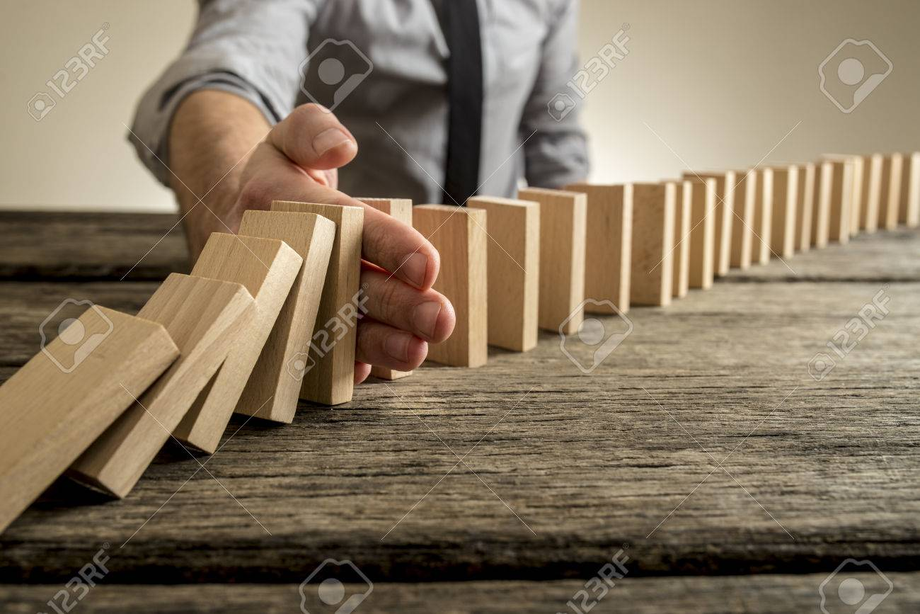 Man stopping domino effect on wooden table. Business success concept. Copy space. - 72873040