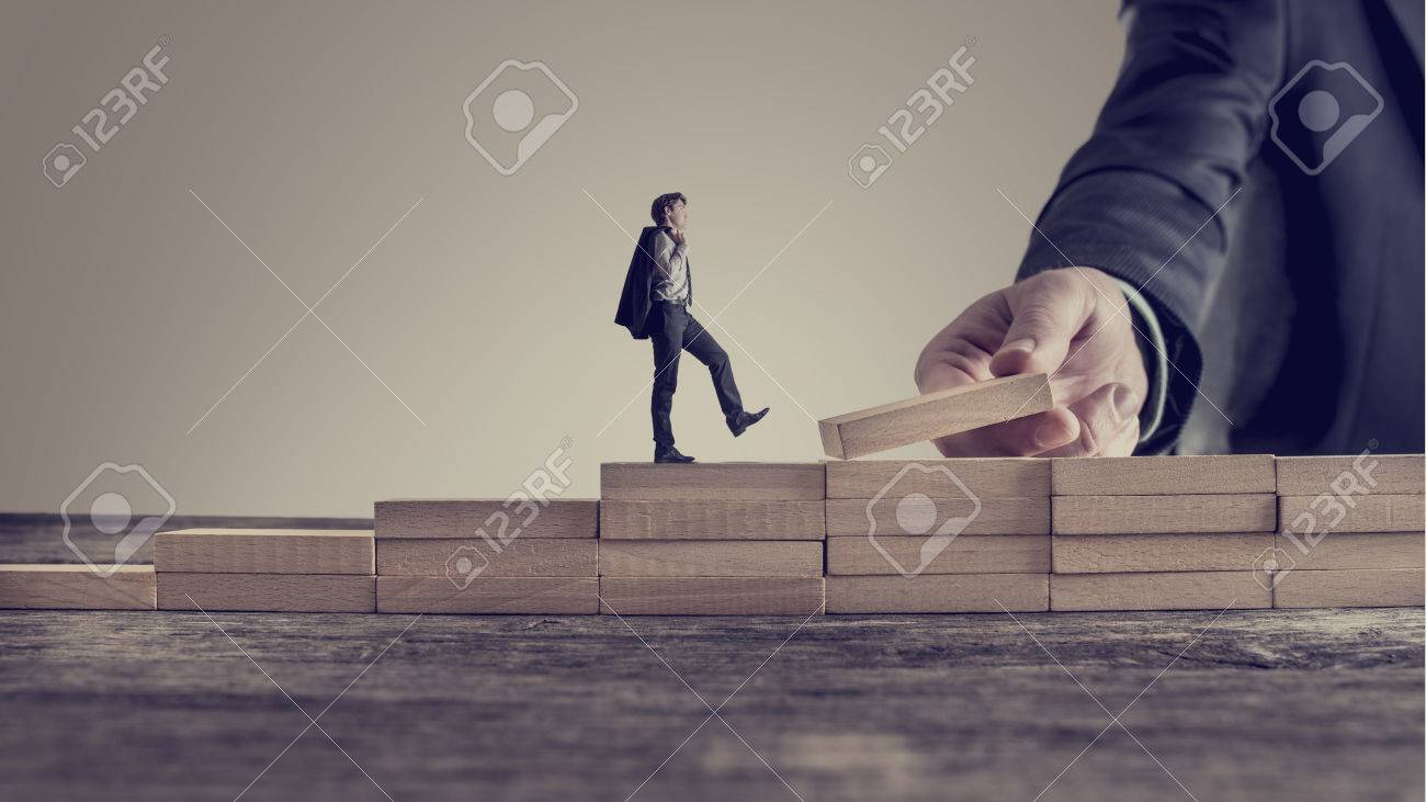 Retro vintage style image of a business person walking up steps, while the hand of other man building stairs for him in a conceptual image of personal and career promotion, leadership and opportunity. - 73152780
