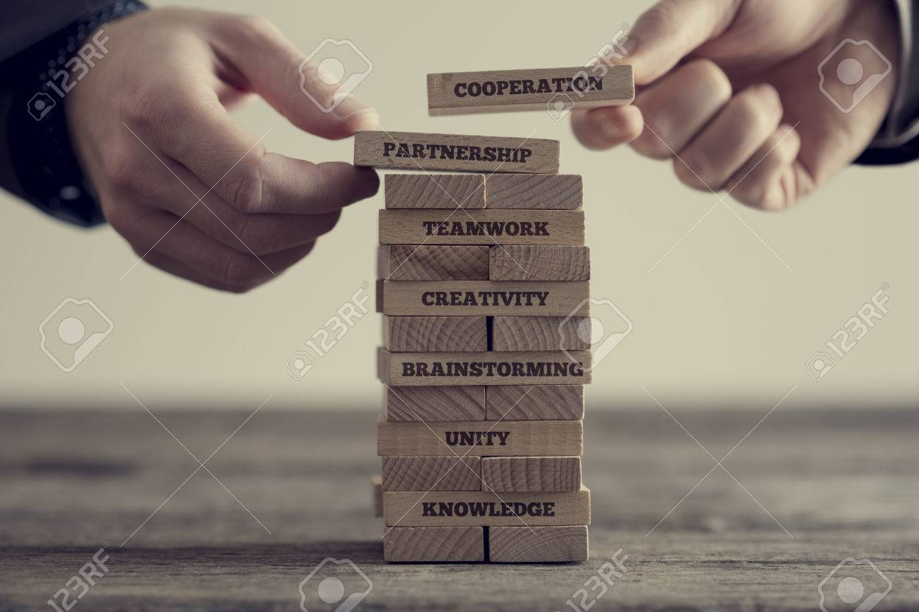 Close-up of hands putting dominoes onto stack of wooden bricks with motivational business signs on brown table surface, vintage effect toned image. - 75223876