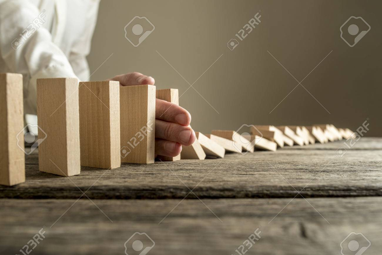 Man in white shirt stopping domino effect on wooden table. Business success concept. - 76556652