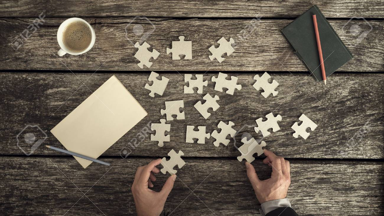 Retro style image of male hands in business suit trying to find a solution to a problem by arranging and matching puzzle pieces on a textured rustic wooden desk, top view. - 81808906