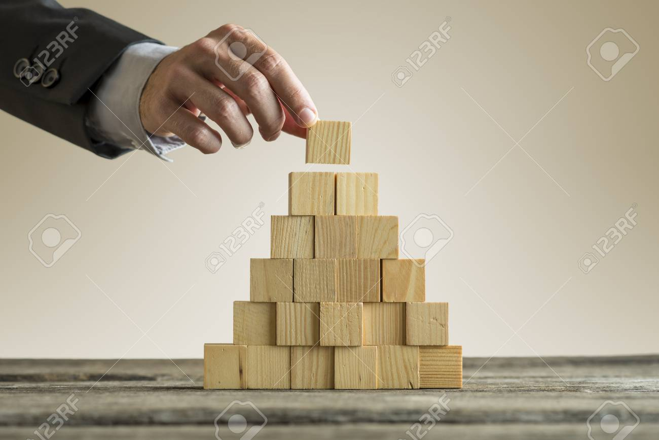 Closeup of businessman making a pyramid with empty wooden cubes. Concept of business hierarchy. - 82248455