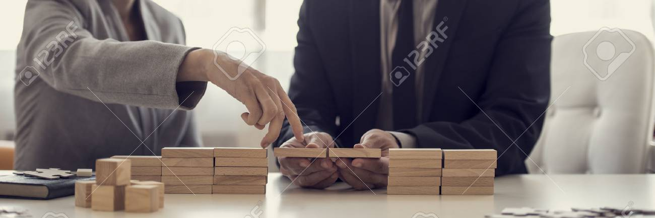 Retro image of businesspeople solving problems by building bridges with wooden blocks to span a gap for partner to walk her fingers across in a conceptual image. - 83126335