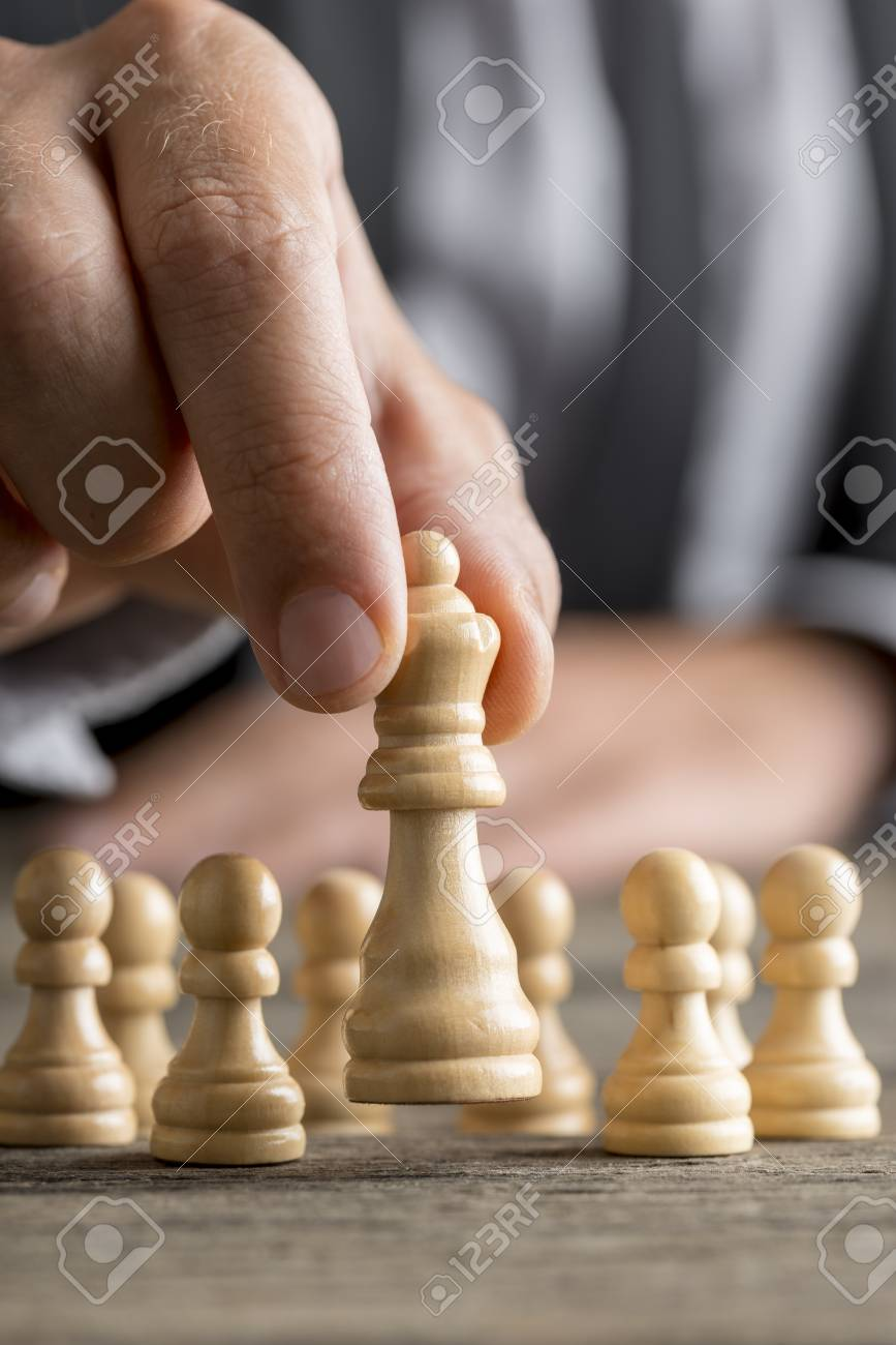Man playing chess moving the queen piece lifting it up in his fingers in a close up view with pawns visible behind on the desk. - 83080499