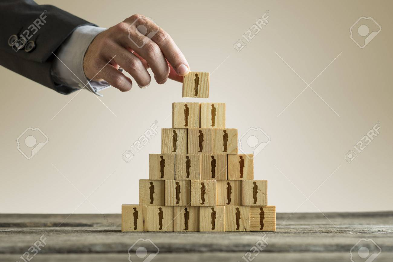 Businessman building a pyramid of wood blocks with people silhouettes, human resources and management concept. - 83039468