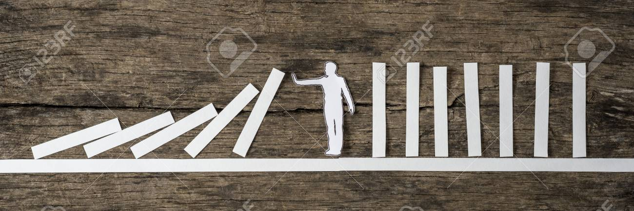 Man stopping the domino effect in a conceptual image of a white paper cutout silhouette on a rustic wood background. - 86028321