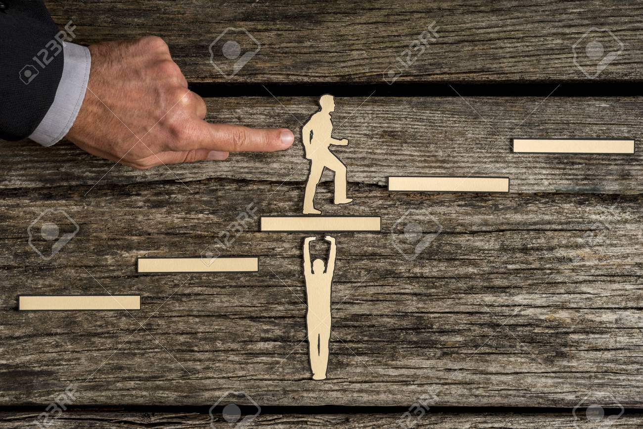 man using his finger pushing small paper figure climbing steps
