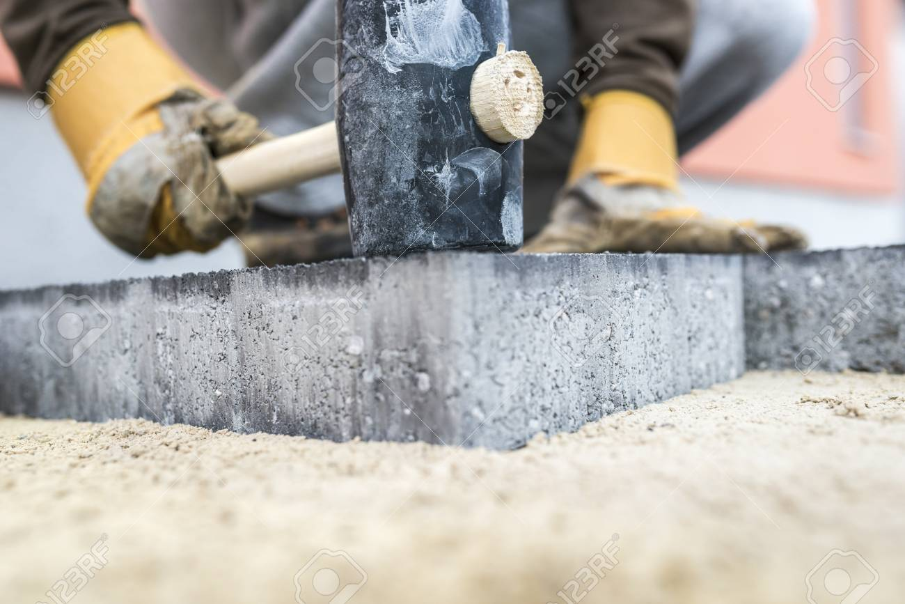 Builder tamping down a new paving slab or brick with a large mallet in a close up view on the hands and tool. - 89489526