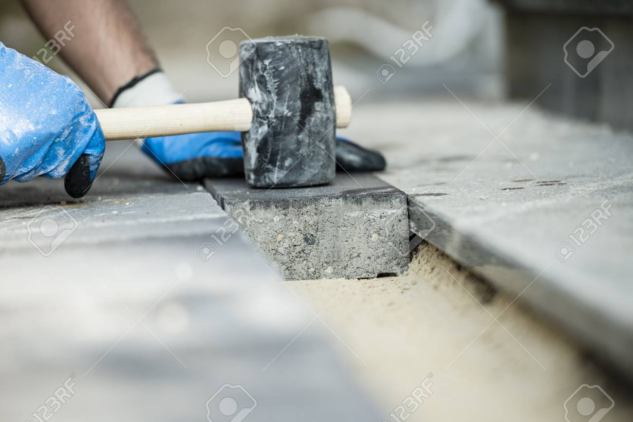Builder Laying A Paving Stone Or Brick Tamping It Down With A Rubber  Mallet. Stock