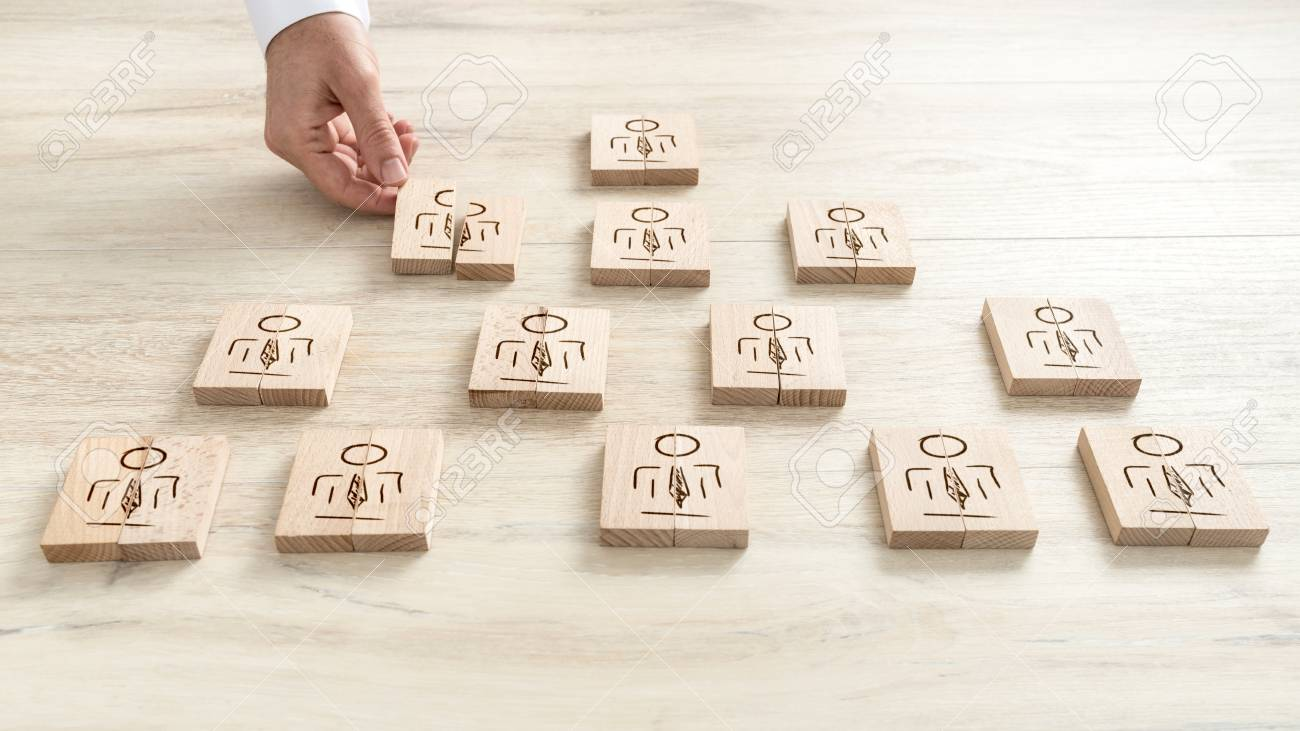 Human resources concept with a businessman arranging a series of wooden blocks depicting people into a pyramid. - 91995270