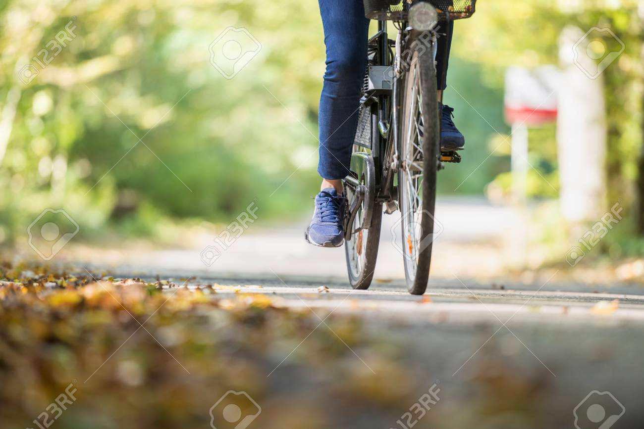 Woman riding a bicycle outdoors on a path in the park in Autumn. - 95651010