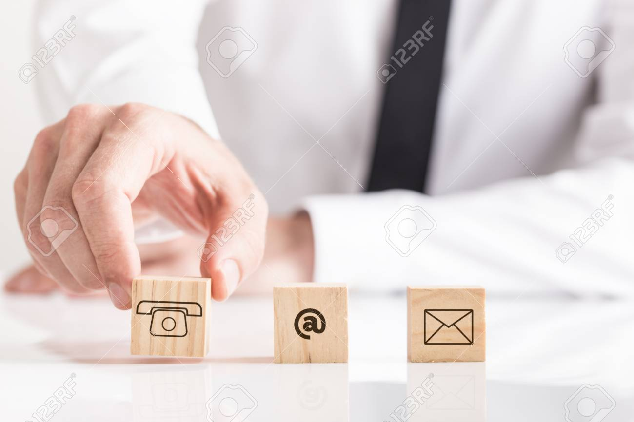 Businessman placing wooden cubes on white table with email and phone pictograms, business contacts conceptual figure. - 102128911