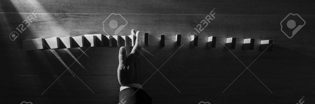 Wide panorama top view of businessman stopping falling blocks on table, monochrome image. - 103049436