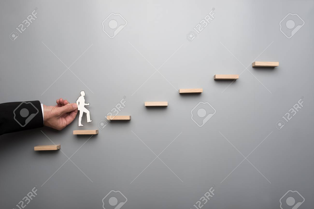 Businessman in white shirt building a graph or ladder of success on grey background. - 103916472