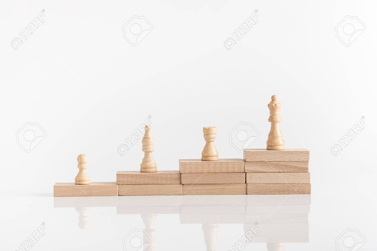 White chess pieces on a stepped stack of wooden blocks with queen piece on the highest level in conceptual image. - 106394688