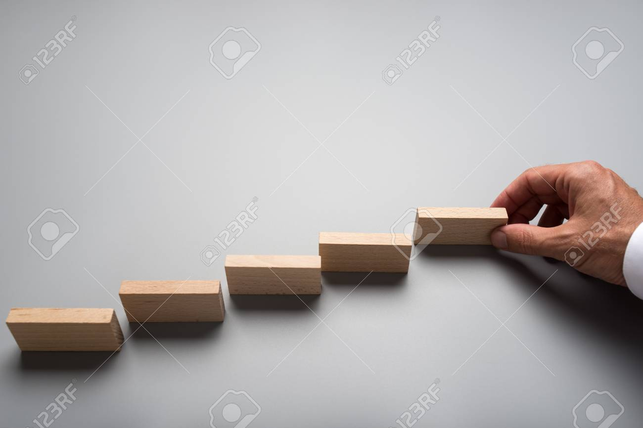 Businessman placing wooden pegs or dominos on grey surface. Conceptual of business vision and start up. - 109027078