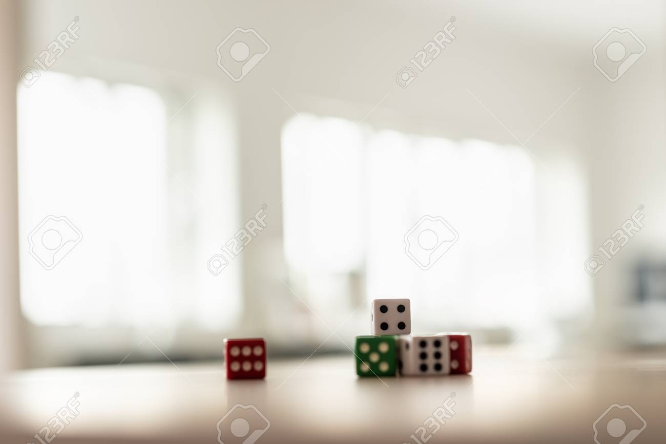 Gaming dice stacked on desk in a bright office. - 109027095