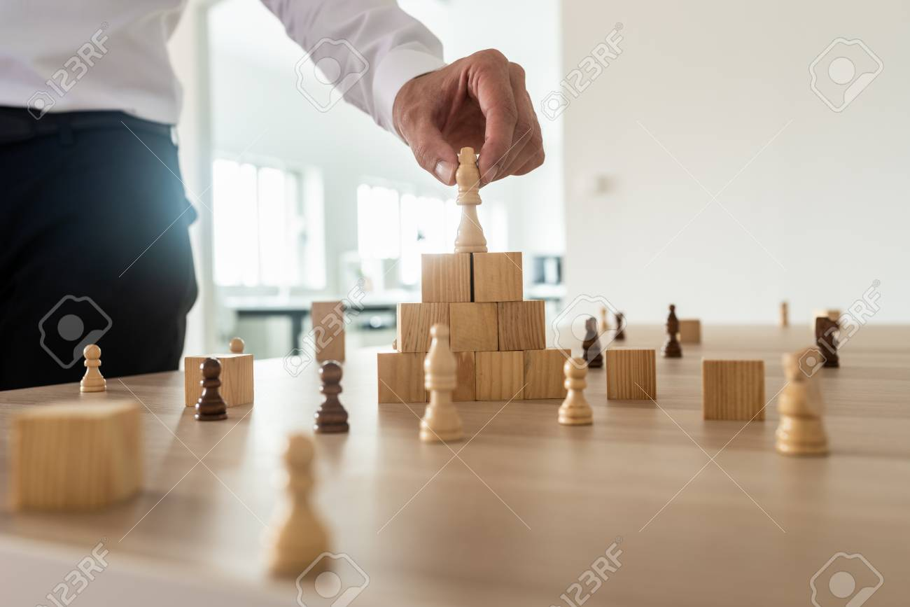 Business hierarchy concept with businessman placing chess figure of king on top of wooden stacked wooden blocks and other figures spread on office desk. - 110301320