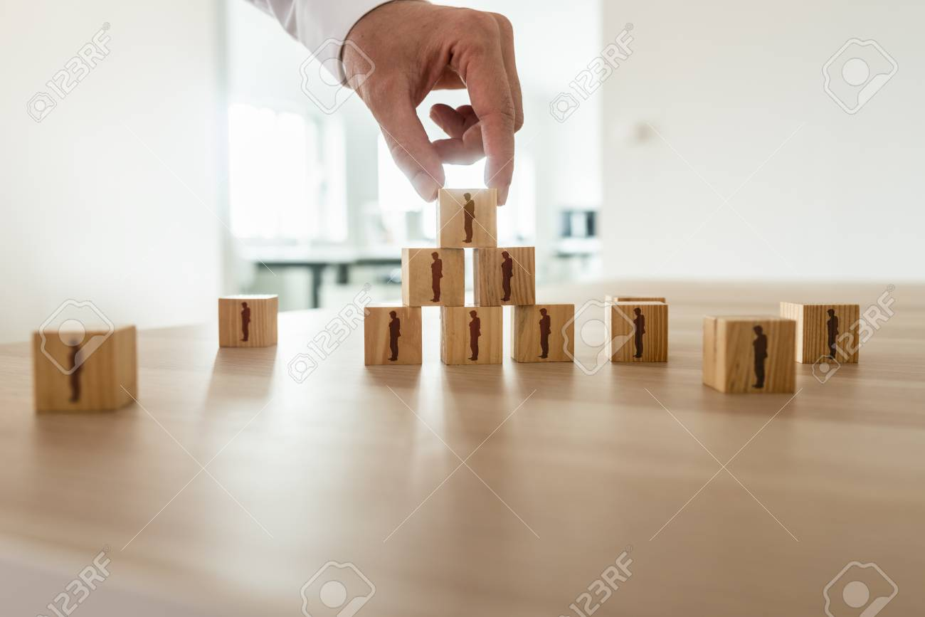 Businessman arranging wooden cubes with people silhouette in a pyramid shape with others scattered on office desk. Conceptual of business organization, human resources and teamwork. - 113034604