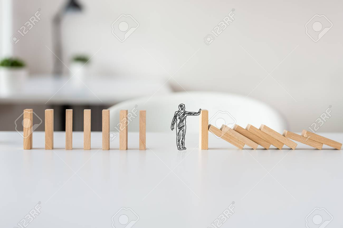 Hand drawn shape of businessman stopping domino effect in a conceptual image of solving business crisis. - 113035031