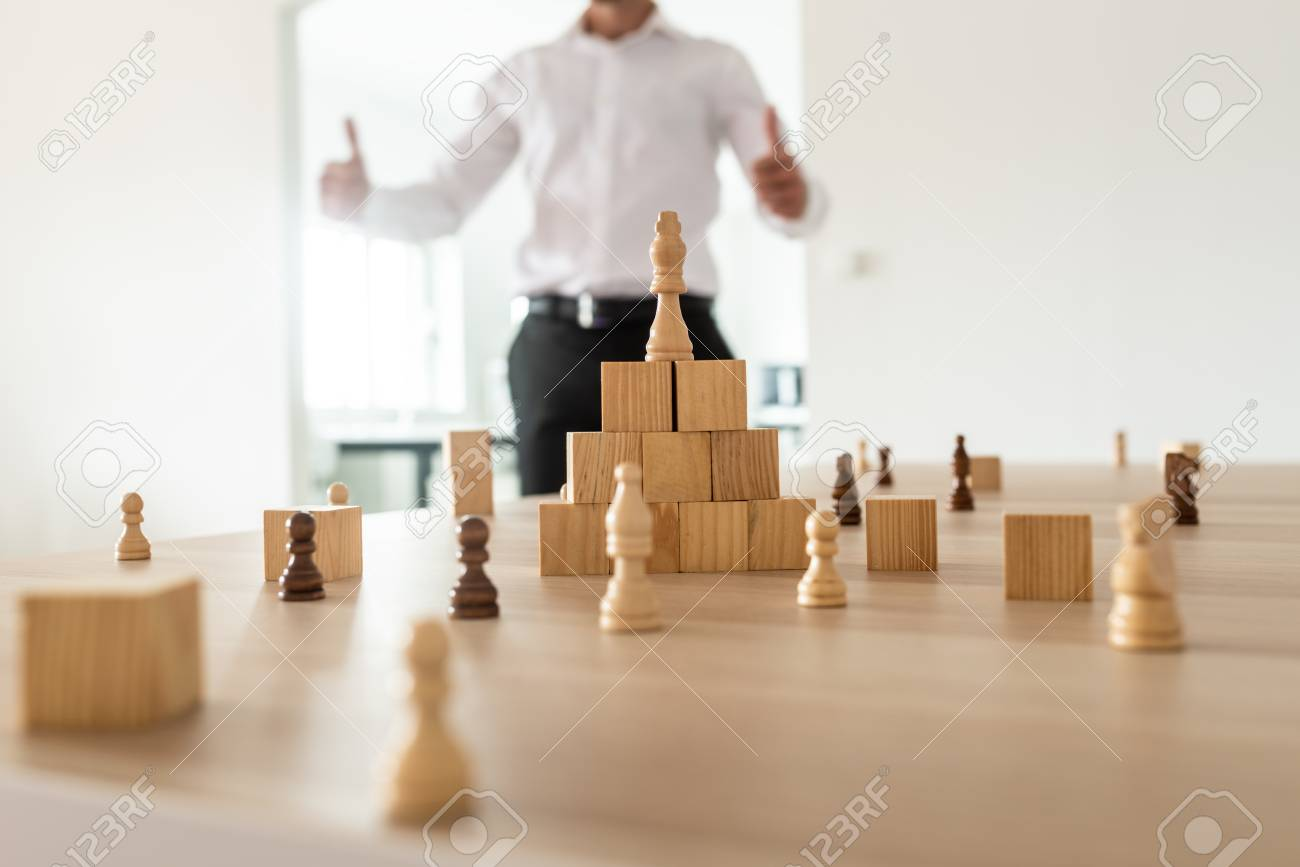 Chess figures and wooden locks positioned on office desk with king on top of a pyramid with businessman in background showing a thumbs up sign. - 119093692