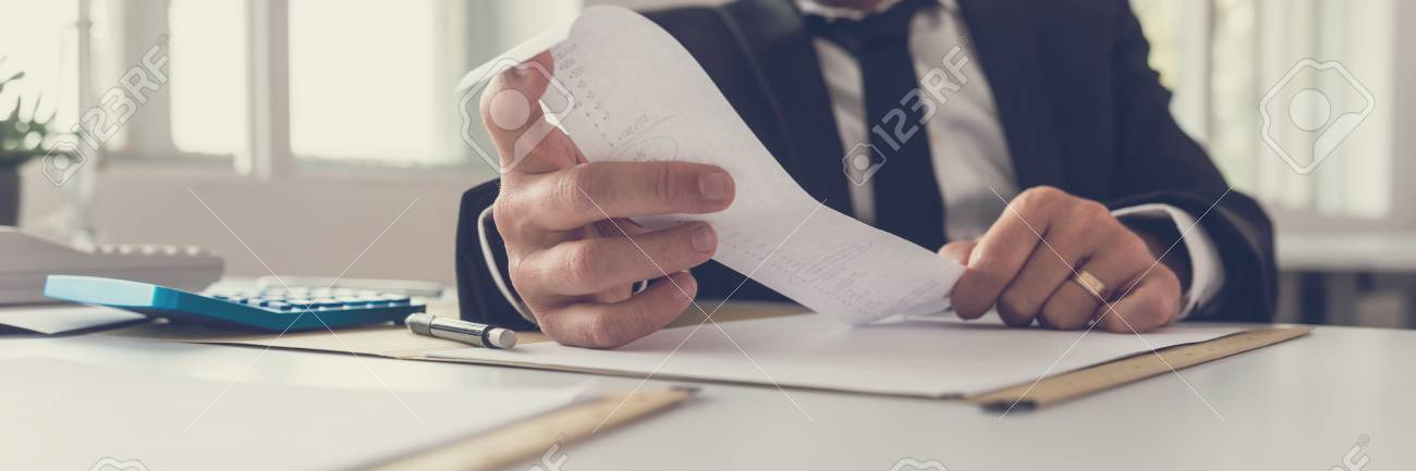 Wide view image of financial adviser sitting at his desk looking at receipt while making an annual balance report. - 120899517