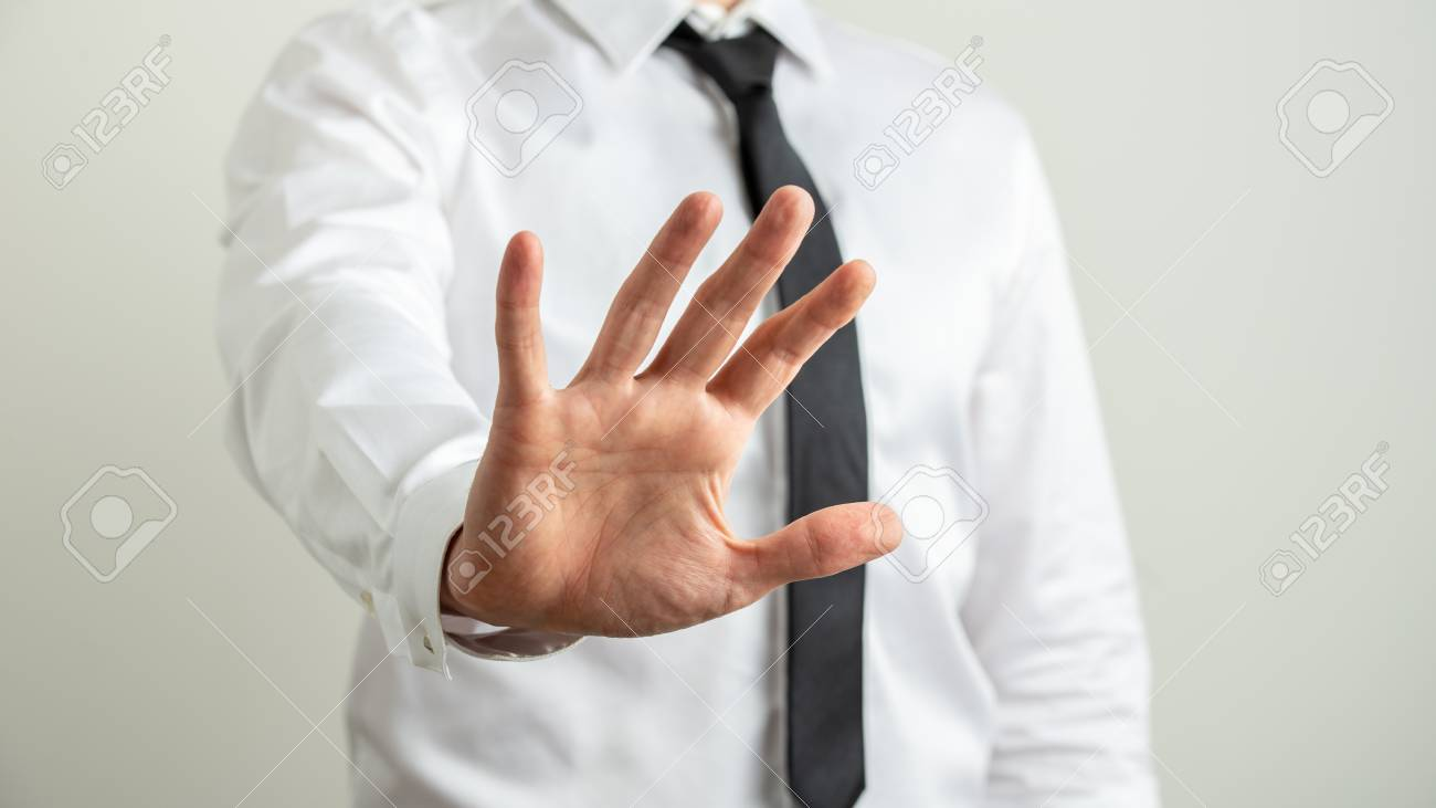 Front view of a businessman making a stop gesture with his hand towards the camera. - 122772735