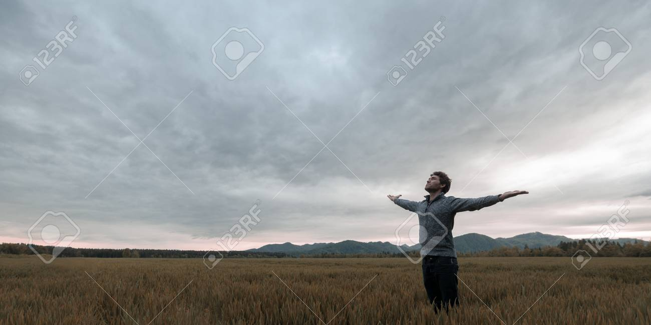 Young man standing in autumn meadow under cloudy evening sky with his arms wide open. - 125306332