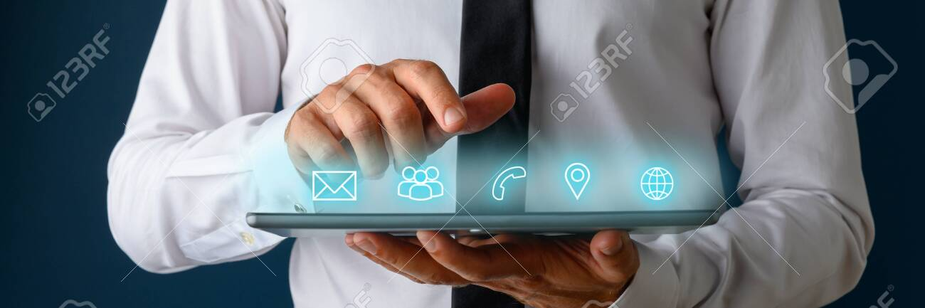 Front view of businessman using digital tablet with icons of contact, communication and location glowing on an interface above the device. - 130111722