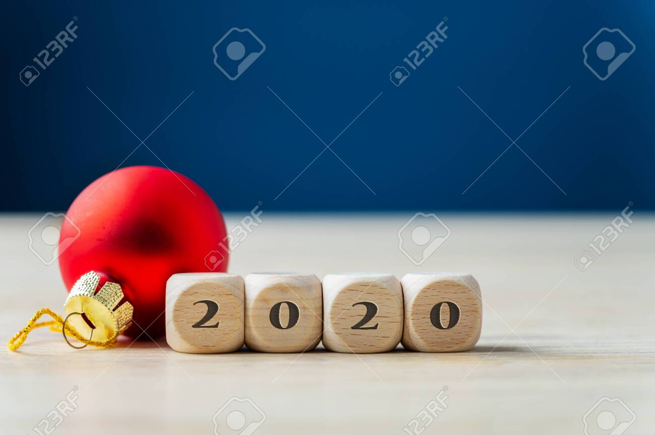 Red holiday bauble next to wooden dices with 2020 sing. Over navy blue background. - 130111847