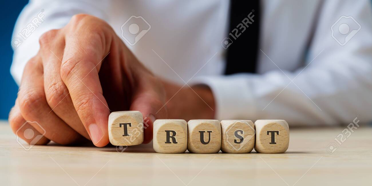 Hand of a businessman assembling the word Trust spelled on wooden dices. - 131447017