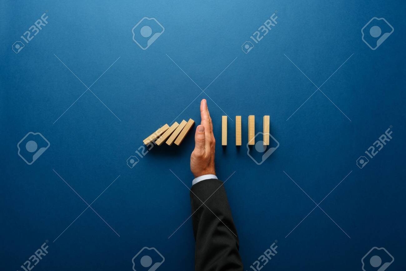 Top view of businessman hand stopping falling dominos in a business crisis management conceptual image. - 131447076