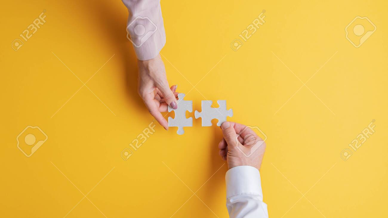 Top view of male and female hands joining two matching puzzle pieces together in a conceptual image. Over yellow background. - 131604808