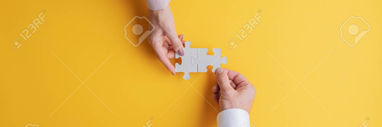 Wide view image of male and female hand joining two matching puzzle pieces together in a conceptual image of teamwork and cooperation. Top view with copy space. - 132536038